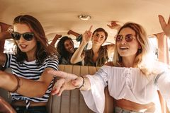 Girls singing and dancing on rod trip. Group of young women singing and dancing in the car on a road trip. Multiracial female friends having fun on a car ride royalty free stock images