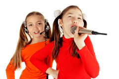 Girls singing into a microphone Royalty Free Stock Photo