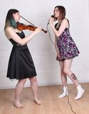 Girls singing and playing violin Stock Image