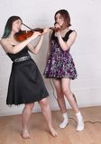 Girls singing and playing violin Stock Photography
