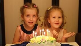 Girls sister on a child`s birthday. Children make a wish and blow out candles on the cake.  stock video footage