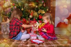 Girls of the sister sort gifts under a Christmas tree. In a photographic studio Stock Photography