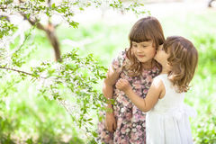 Girls sister with spring flowers, tender and love Royalty Free Stock Images