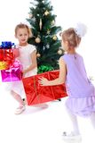Girls sisters around the Christmas tree fuss. Considering boxes with gifts-isolated on white background Royalty Free Stock Photo