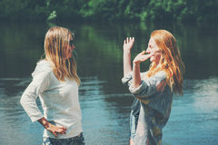 Girls sisters couple traveling together walking at lake. Happy emotions talking Fashion Lifestyle concept young women enjoying having fun stock images