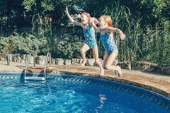 Free Girls Sisters Diving In Water On Home Backyard Pool. Children Siblings Friends Enjoying And Having Fun In Swimming Pool Together. Stock Photos - 195446913