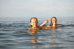 Girls sisters have fun bathing in the sea royalty free stock photo