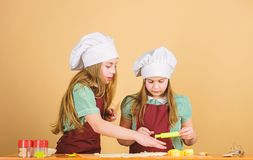 Girls sisters having fun ginger dough. Kids baking cookies together. Kids aprons and chef hats cooking. Homemade cookies. Best. Family recipe. Cooking skill stock photo