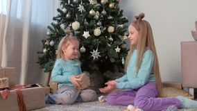 Girls sisters shaking box with present and playing sitting near Christmas tree. They throwing box to each other. Xmas eve at home in living room with stock video