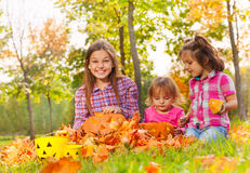 Girls sit in autumn park together with pumpkins Royalty Free Stock Images