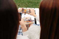 Girls sit on a bench and shoot gifts Stock Image