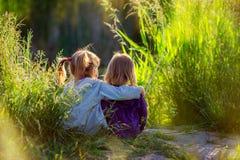Girls sit having embraced ashore. At sunset Stock Photography