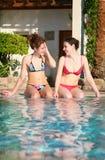 Girls sit at pool. Girls in bikini sit at pool royalty free stock photo