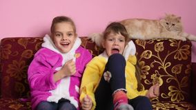 Girls sit on the sofa, lick lollipops and watch TV, TV suddenly turned off stock video footage