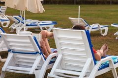 The girls sit in the sun loungers on the lawn on a summer day. Back view royalty free stock images