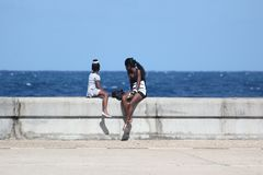Girls sit on the waterfront and look at the ocean in Havana Cuba royalty free stock photos