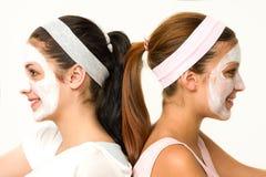 Girls sitting back-to-back wearing facial mask. Girls sitting back-to-back wearing white facial mask Royalty Free Stock Photo