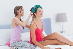 Girls sitting in bed one wearing hair rollers Stock Images