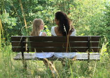 Girls sitting on a bench Royalty Free Stock Image