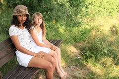 Girls sitting on a bench. Two girls in white clothes - little caucatian barefooted kid and tropical women sitting on wooden bench Stock Photo