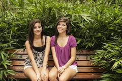 Girls sitting in a bench. Two young women sitting in a bench in a beautiful park of Houston in a summer day Royalty Free Stock Image
