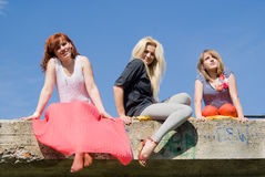 Girls sitting on the bridge Stock Photo
