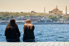 Girls Sitting At Coastline, Istanbul, Turkey Stock Photos