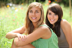 Girls sitting in a field Stock Images