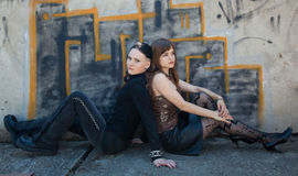 Girls sitting in front of graffiti wall Stock Photo