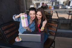 Girls sitting in front of laptop and smiling Royalty Free Stock Photos