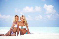 Girls sitting on ocean coast Royalty Free Stock Photography
