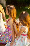 Girls sitting outdoor and doing hairstyles at park Royalty Free Stock Photos