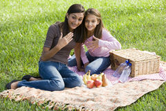 Girls sitting on picnic blanket on grass in park Royalty Free Stock Photos
