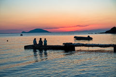 Girls sitting on a pier at sunset in Sithonia Stock Photos
