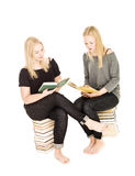 Girls sitting on piles of books Stock Photos