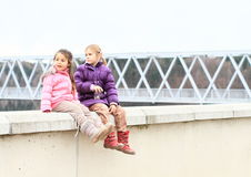 Girls sitting on railing of dam Royalty Free Stock Photo
