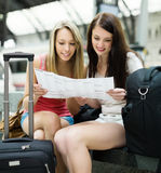 Girls sitting at railroad station with map Royalty Free Stock Photo