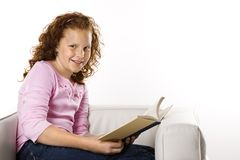 Girls sitting reading book. Stock Photos