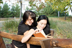Girls sitting reading a book Royalty Free Stock Photo