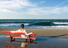 Girls sitting on a red bench on the beach Stock Photo