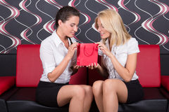 Girls sitting on red sofa with gift Stock Images
