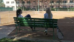 Girls sitting and resting on bench on a tennis field after playing a match. Girls sitting and resting on a bench on a tennis field after playing a match stock footage
