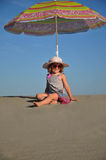 Girls sitting on the sandy beach under a beach umb. Rella,summer Royalty Free Stock Images