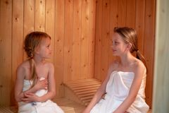 2 girls are sitting in the sauna and looking at each other stock image