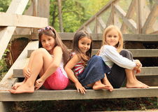 Girls sitting on stairs. Three barefoot girls sitting on wooden stairs Royalty Free Stock Image