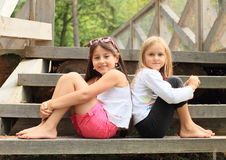 Girls sitting on stairs. Two barefoot girls sitting on wooden stairs royalty free stock image
