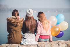 Girls sitting on the stone wall and looking at the river. Three girls sitting on the stone wall and looking at the river Stock Photos