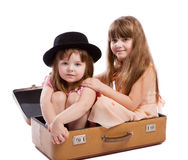 Girls sitting in suitcase Stock Photos