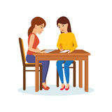 Girls sitting at table decide working moments, discuss, exchange materials. Royalty Free Stock Images