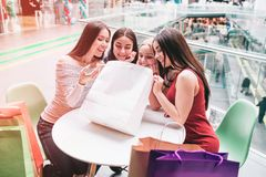 Girls are sitting at the table and looking into shopping bag. They are happy and very excited. Girls are sitting at the table and looking into shopping bag stock images